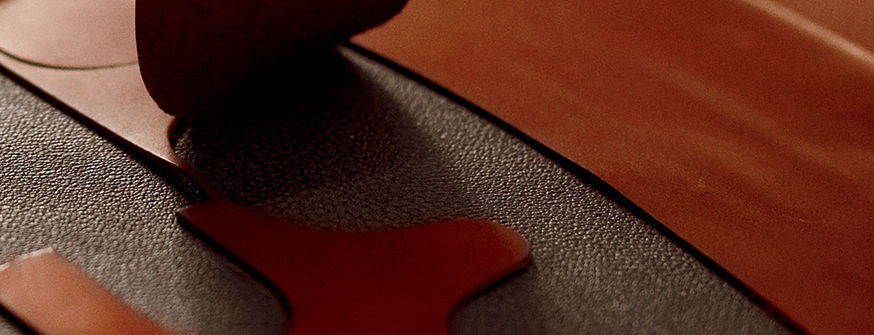 Close-up image of black fabric & tan pieces of leather