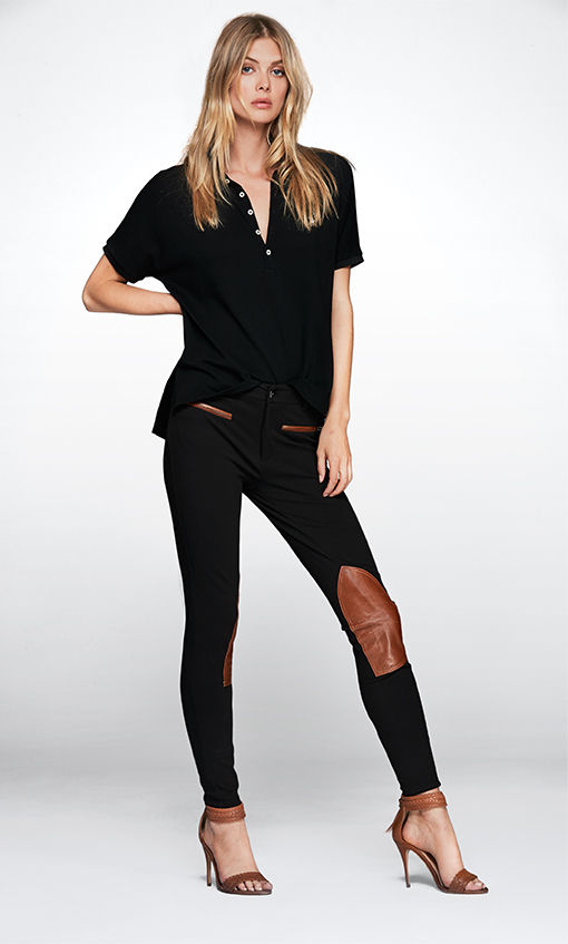 Woman models black jodhpur-inspired pants with tan leather knee patches