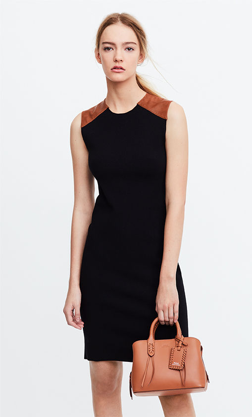 Woman in black sleeveless sheath dress with tan leather patches at shoulders