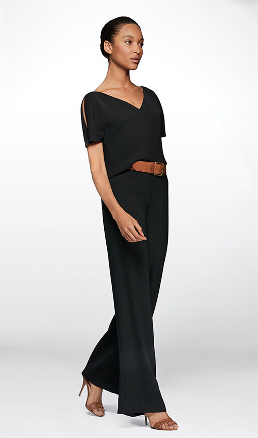 Woman in short-sleeve black jumpsuit paired with brown leather belt