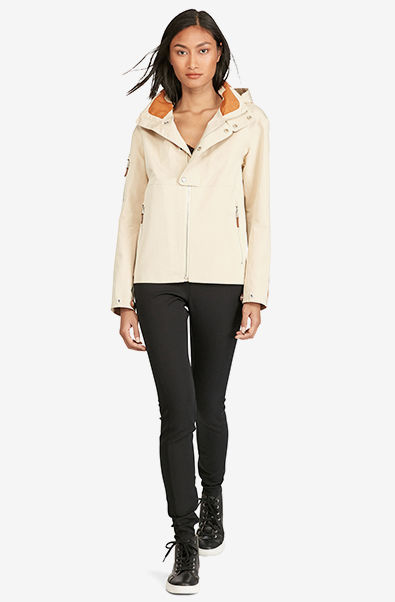 Woman in cream jacket with leather accents, black pants & high-tops