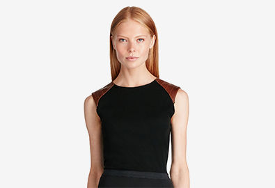 Woman in black sleeveless top with leather shoulder patches