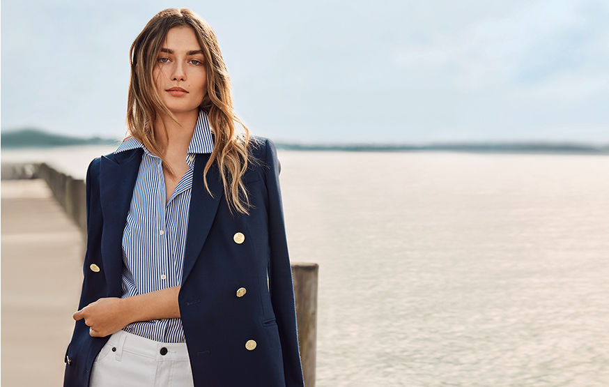 Woman on boardwalk in navy blazer, striped shirt & white pants