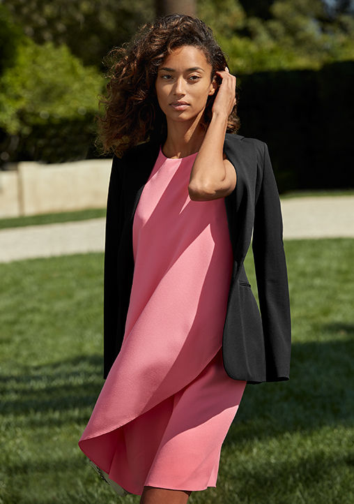 Woman models pink dress with an asymmetrical overlay