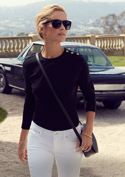 Woman walks in black button-shoulder top & white jeans