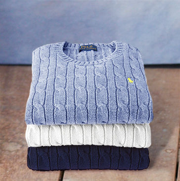 Stack of folded cable-knit sweaters in light blue, white, and navy.