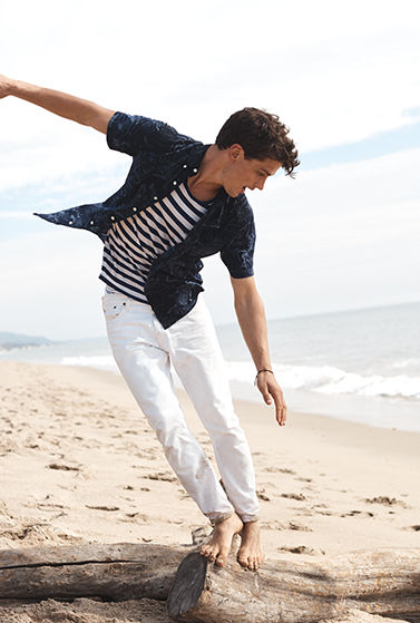 Man balances on rock wearing jeans & tee under unbuttoned shirt
