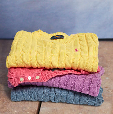 Stack of folded cable-knit sweaters in yellow, pink, purple, and blue.
