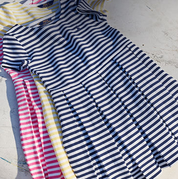 Neat pile of striped dresses in blue, yellow, and pink.