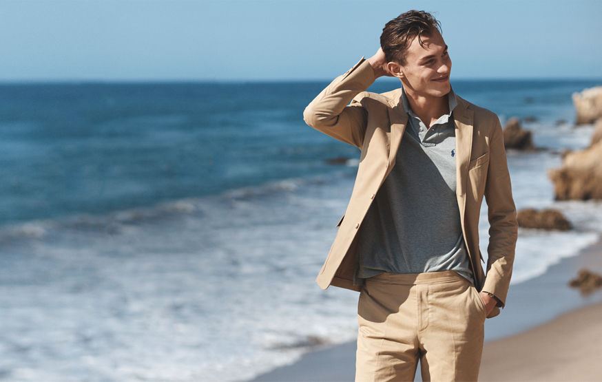 Man walking on beach in sport coat, Polo shirt & tan pants