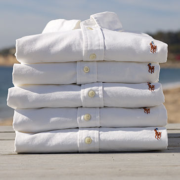 Stack of white oxford shirts with multicolored Polo Pony embroidered at chest