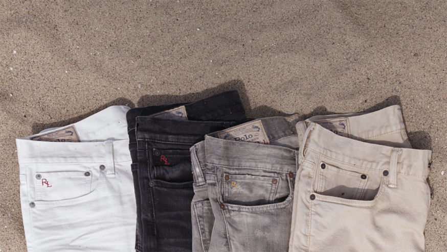 Row of folded jeans in various hues, from white to grey