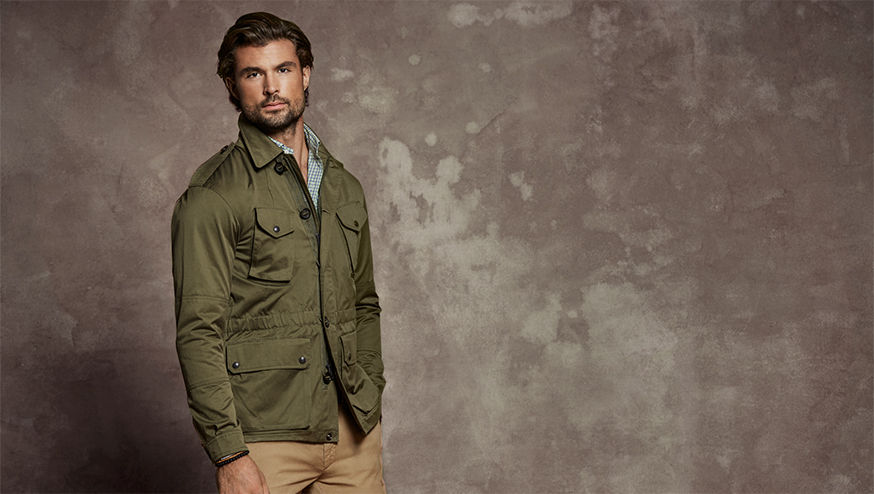Man models army green utility jacket & tan chinos