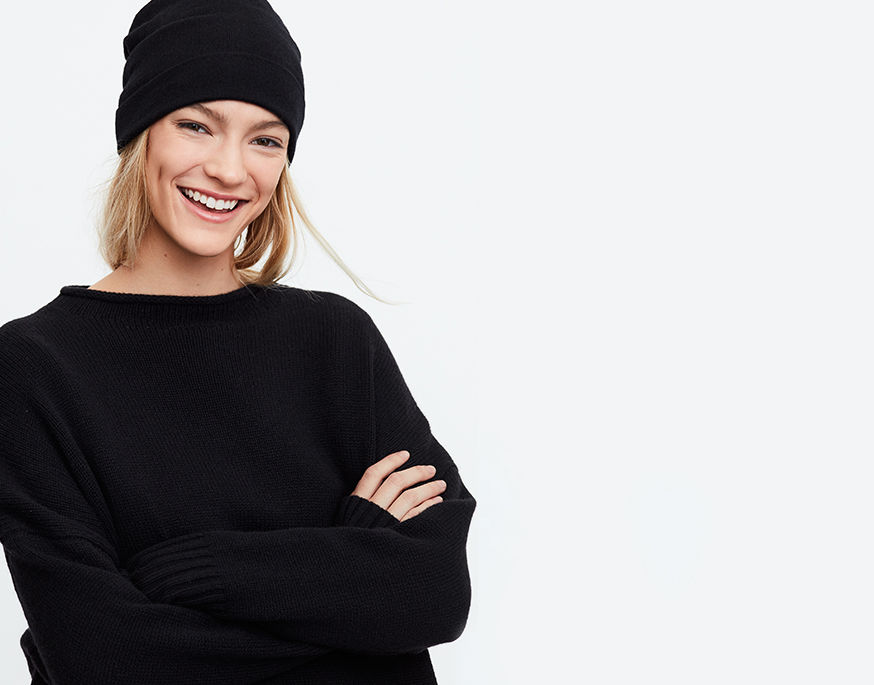 Woman with arms crossed wears black beanie & oversize sweater