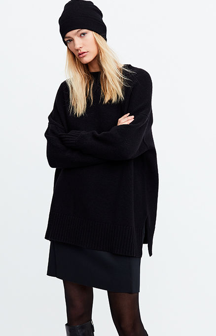 Woman models black beanie & oversize sweater worn over dress