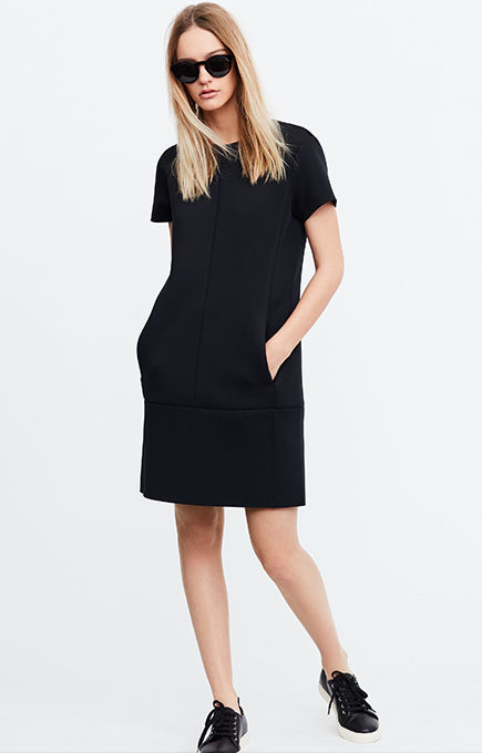 Woman in shades models black short-sleeve dress worn with sneakers