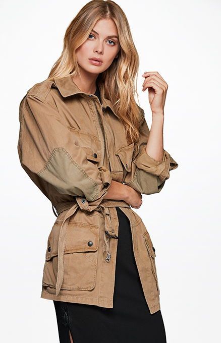 Woman models tan elbow-patch utility jacket over black dress