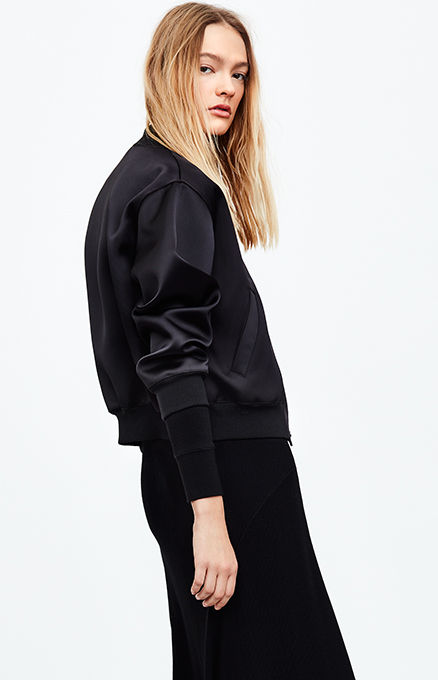 Woman in black varsity-inspired jacket layered over ankle-length dress