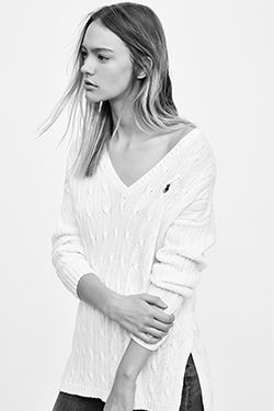 Woman models side-slit cable-knit sweater in white.