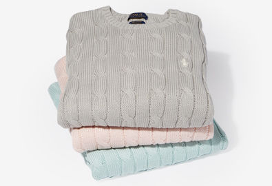 Stack of cable-knit crewneck sweaters in grey, light pink, and green