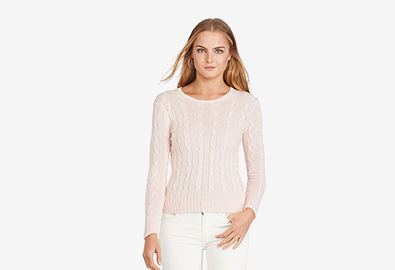 Model wears light pink cable-knit crewneck sweater and white jeans.