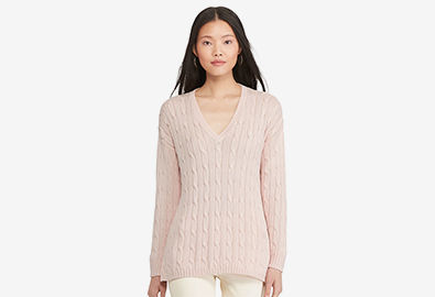 Woman wears pink side-slit cable-knit V-neck sweater