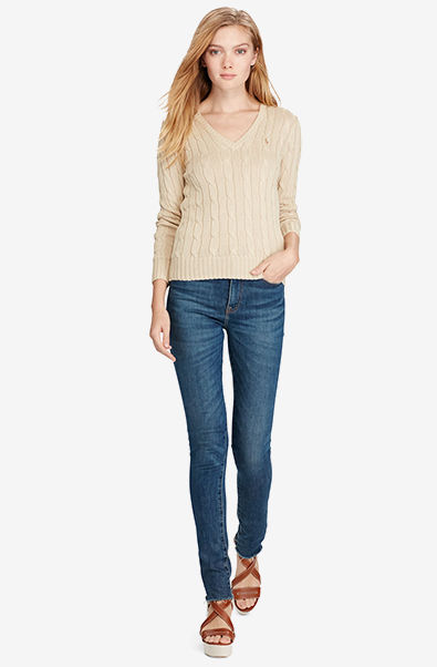 Woman models tan cable-knit V-neck sweater & jeans.
