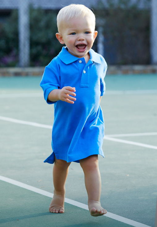 Baby runs while wearing blue oversize Polo shirt.