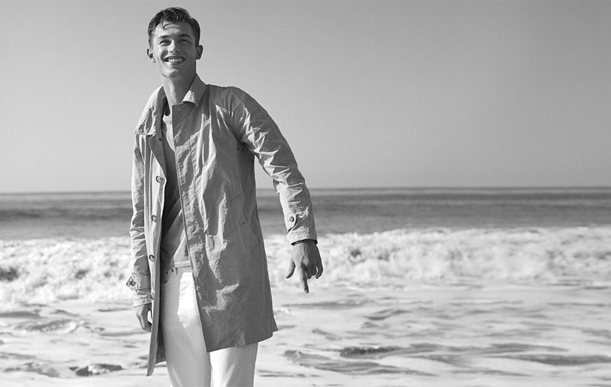 Black & white image of man on beach in lightweight jacket