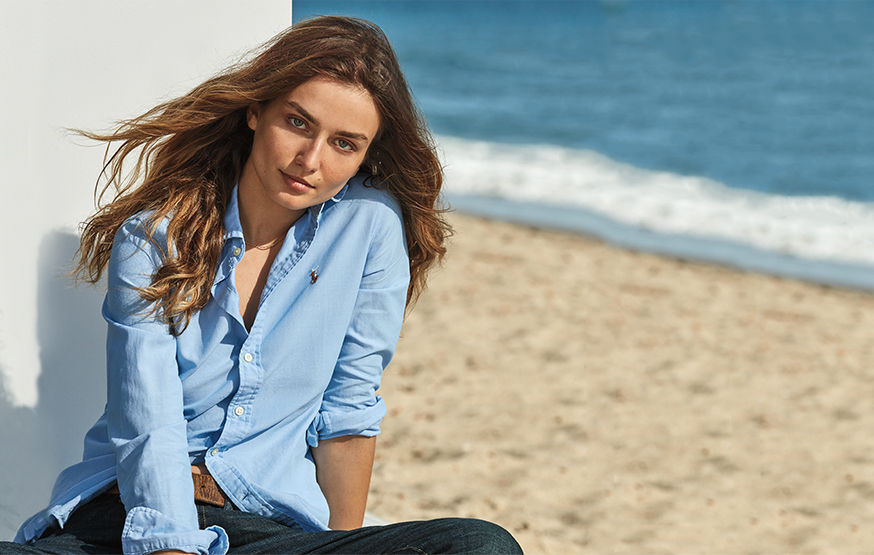 Woman sits on beach in relaxed light blue oxford shirt