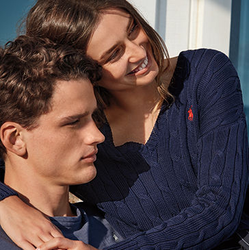 Woman in cable-knit V-neck sweater with arms around man