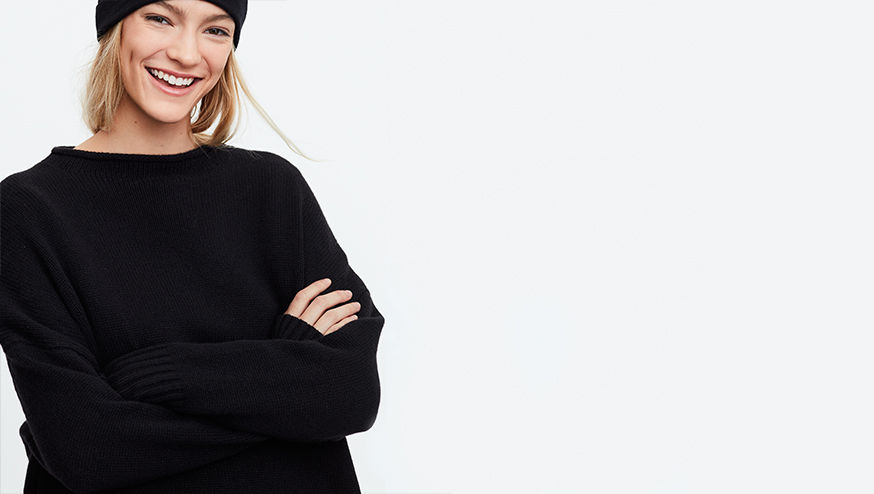 Smiling woman wears black beanie & oversize sweater