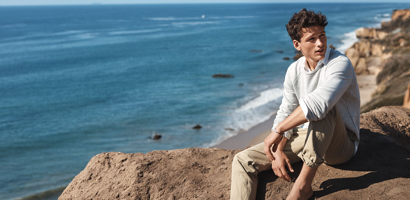 Man sits on rocks by ocean in terry sweatshirt & chinos
