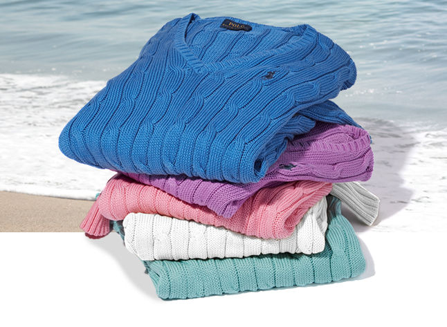 Stack of cable sweaters in blue, violet, pink & mint green