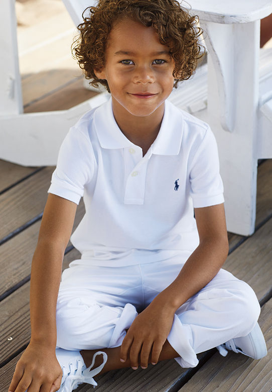 Boy wears all-white outfit of Polo shirt, pants, and sneakers.