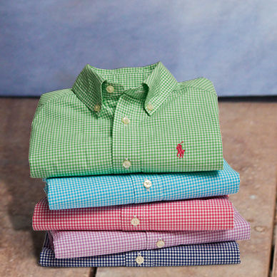 Stack of folded checked button-down shirts in an array of colors.