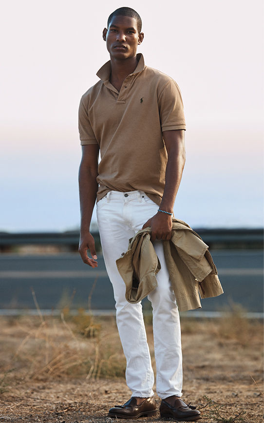 Man models tan Polo shirt and white jeans