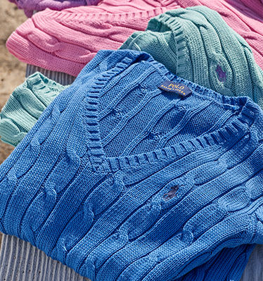 Stack of folded blue, green & pink cable V-neck sweaters