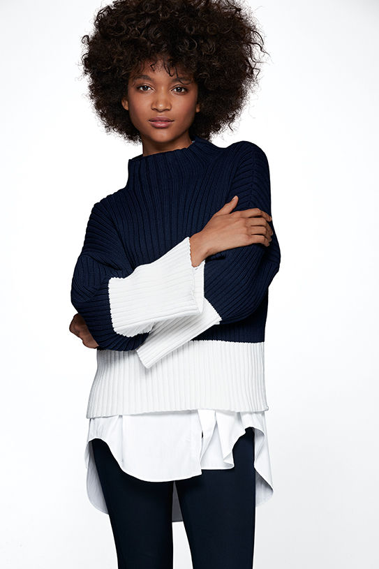 Woman with arms crossed models sweater worn over white shirt