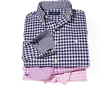 Stack of folded gingham checked shirts in spring hues