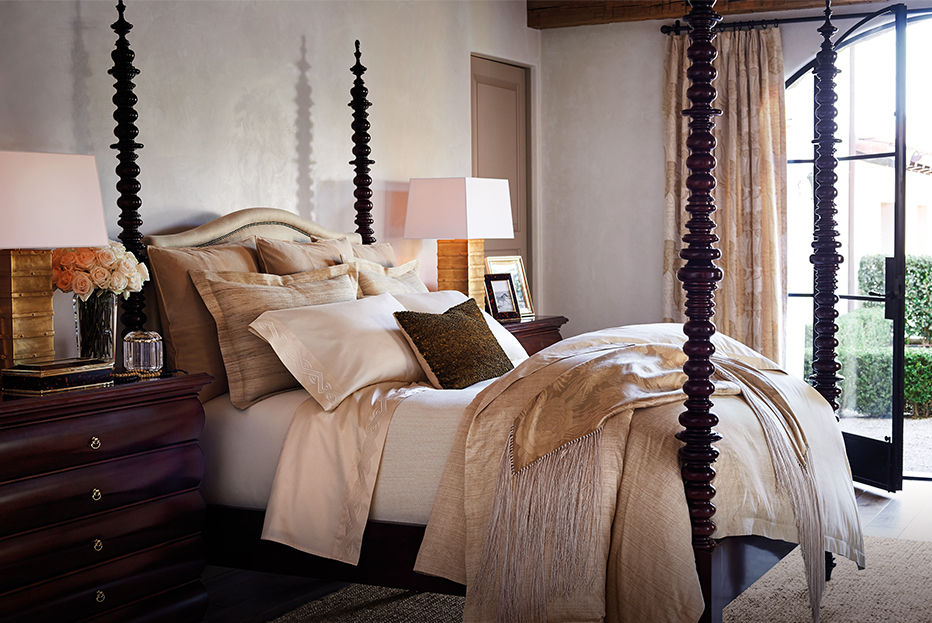 Artfully made bed with textured. neutral-hued linens accented with gold