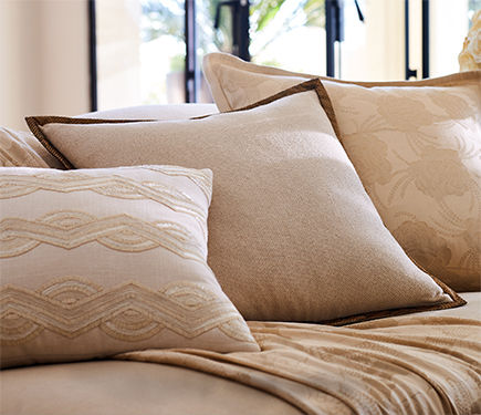 Cream-colored throw pillows with various textures and patterns