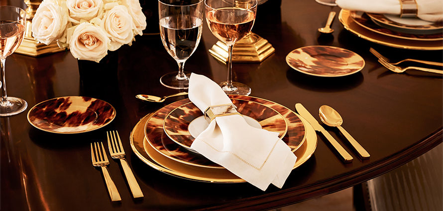 Table set with gold-tone flatware & tortoiseshell-patterned plates