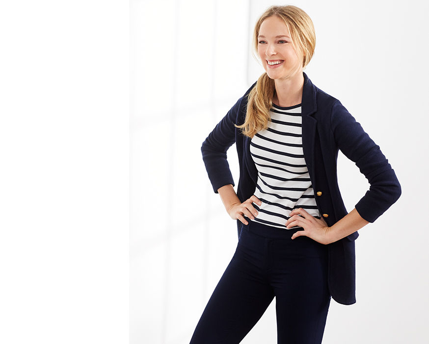 Woman stands with hands on hips modeling navy sweater blazer