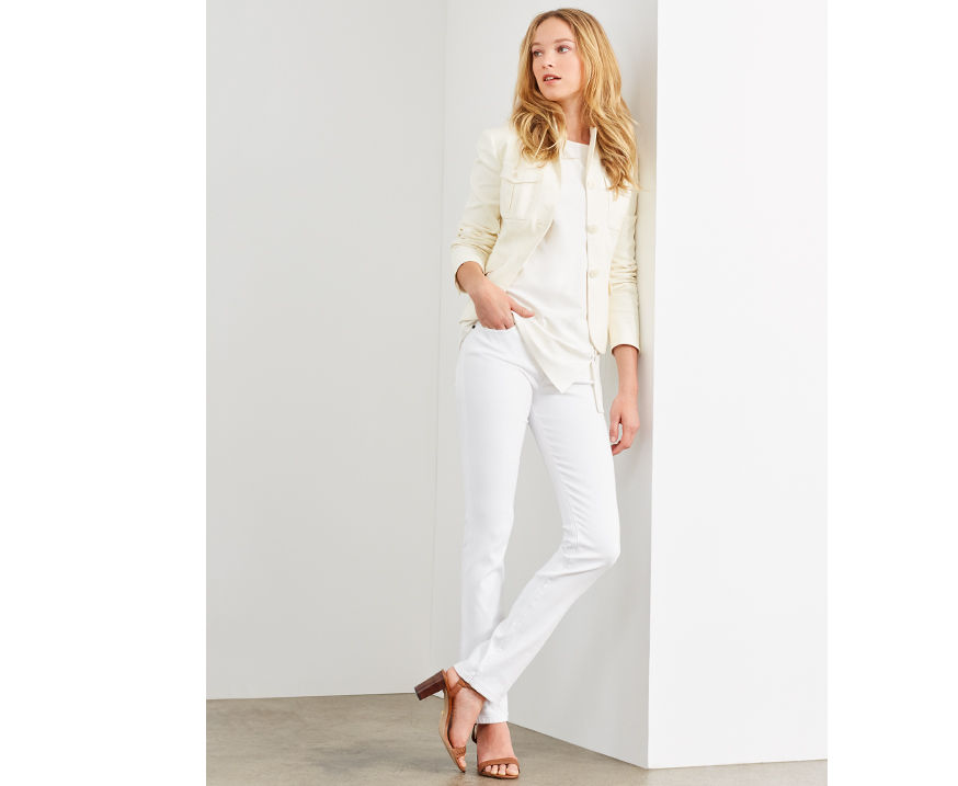 Woman models cream jacket worn with white jeans & tan leather heels