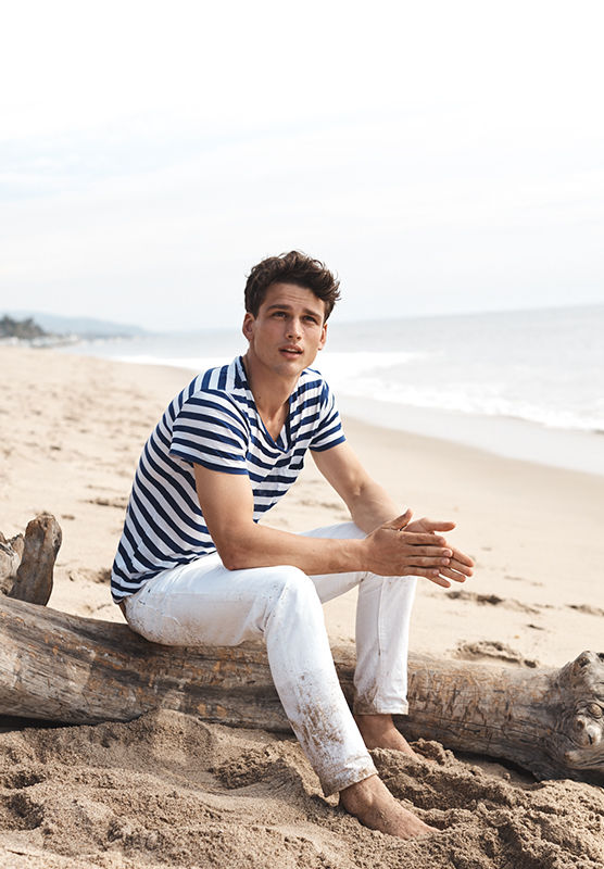 Barefoot man on beach in navy-and-white striped tee