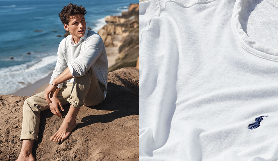 Man in grey sweatshirt & chinos sits on rocks near beach