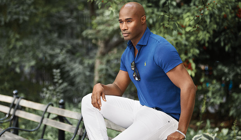 Man models royal blue Polo shirt paired with white jeans