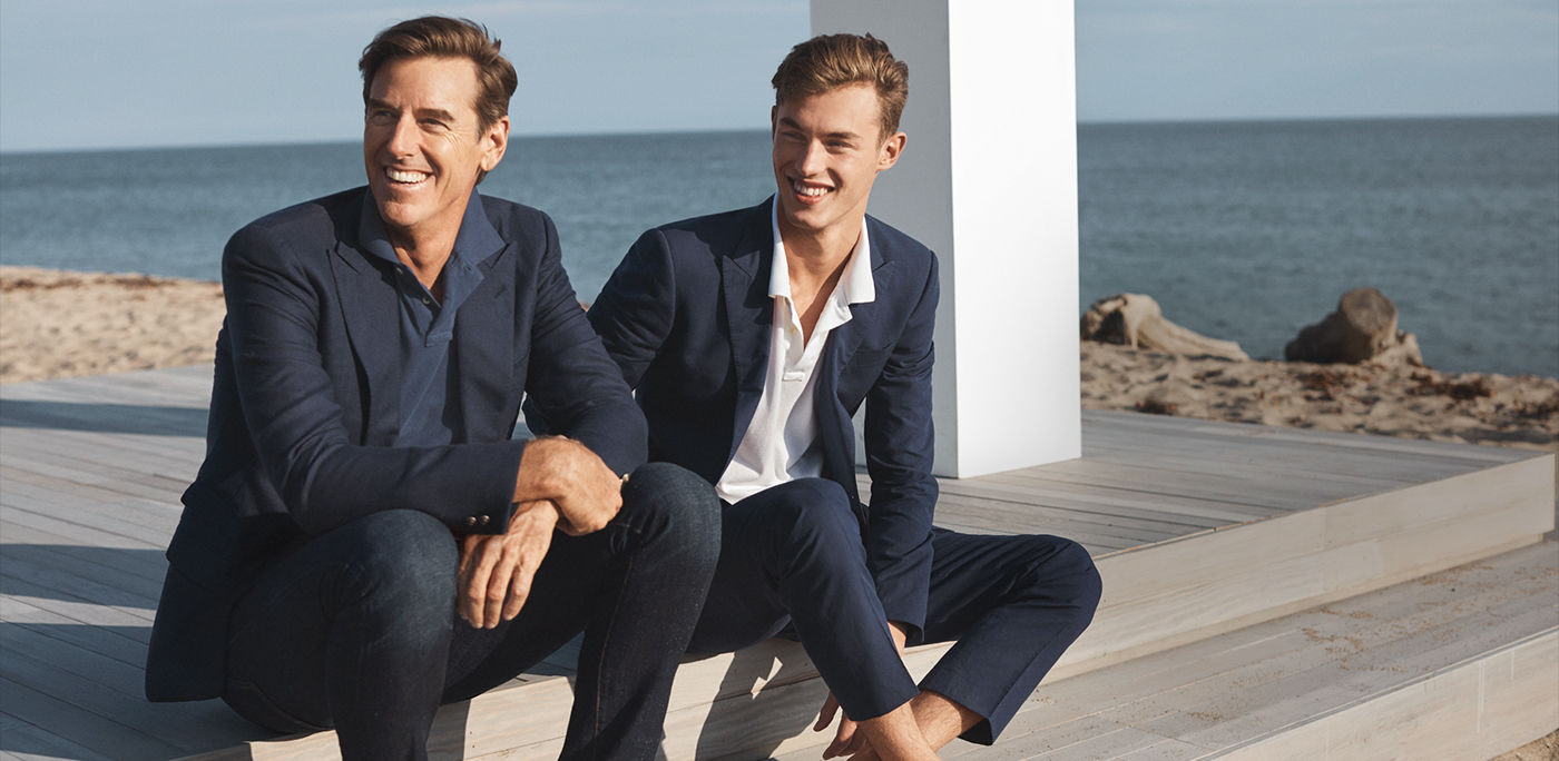 Two men in navy suiting sitting near beach