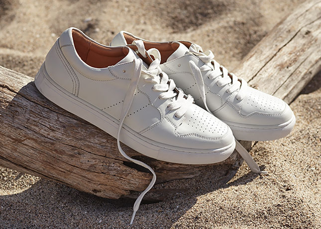 Pair of white lace-up sneakers on beach